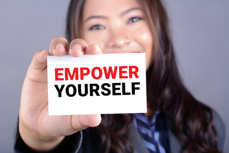 Empwer yourself message on a card held by a young asian woman